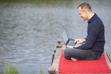 mann mit computer auf dem steg