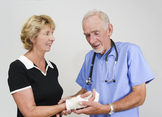 Doctor attending old woman with hand in cast