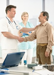 Doctor congratulating senior patient on recovery