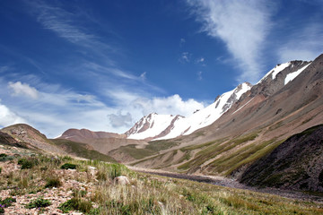 Valley in mountains against ridge and blue sky. Tien Shan