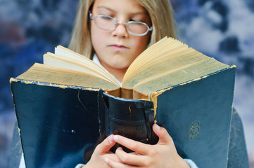 Student. Serious girl read an old book. Focus on the book