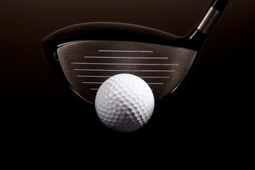 a close-up of a golf driver and golf ball on black