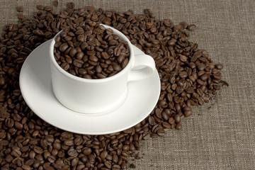 white mug on coffee beans and sacking