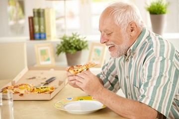 Smiling older man eating pizza slice