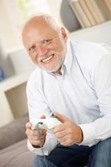 Portrait of modern senior playing computer game