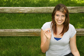 pretty teen girl smiling outside by fence