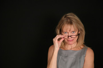 smiling woman looking over glasses