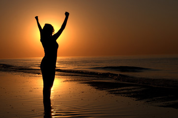 Silhouette of a woman showing achievement on a beach sunset