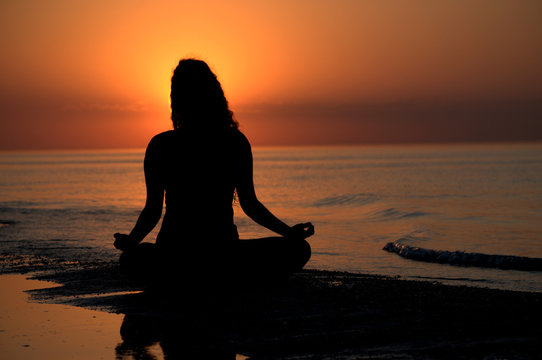 Silhouette of a woman doing yoga by the sunset on the beach