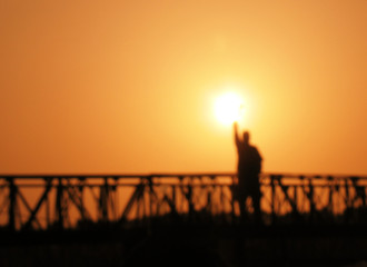 a man stands on a bridge on sunset