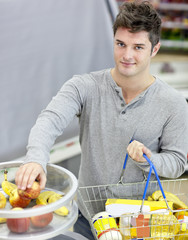 Healthy man with shopping-basket buying fruits in a grocery shop