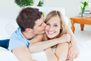 Portrait of an attentive man kissing his girlfriend at home
