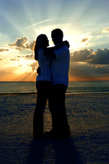 Silhouette couple embrace in the rays of the sun