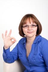 Девушка в очках показывает знак OK