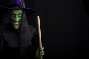 Scary witch holding a broomstick