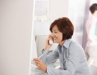 Mature businesswoman talking on landline phone