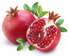 Juicy pomegranate and its half with leaves.
