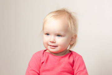 Portrait of cute young baby sit on chair and  grimacing