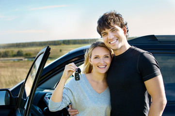 Happy young people near new car on nature