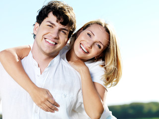 beautiful young smiling couple on blue sky background