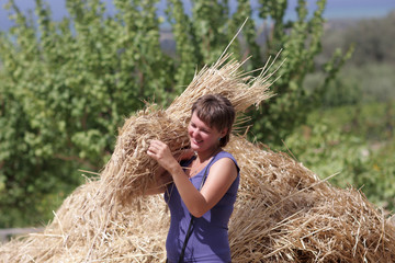 Happy woman with armful of wheat