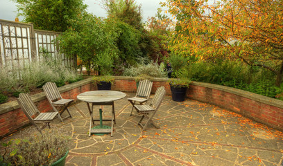 English country garden scene with chairs and bench in Autumn Fal