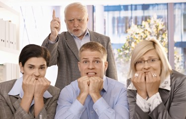 Angry boss shouting at scared employees