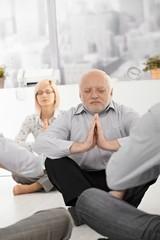 Senior businessman meditating in office