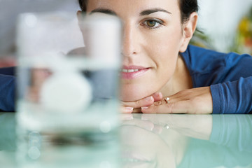 woman looking at aspirin in glass of water