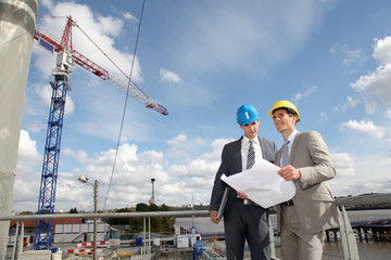 Businessmen checking plan on construction site