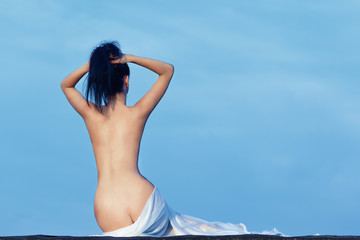 woman bare back sitting wrapped with white towel