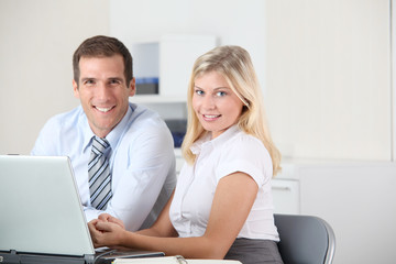 Man and woman working in the office on laptop computer