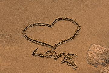 Herz der Liebe im Sand gezeichnet mit Steinen umgeben.