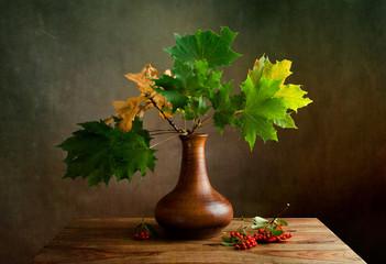 Herbstliches Stilleben mit Ahornblättern und Beeren