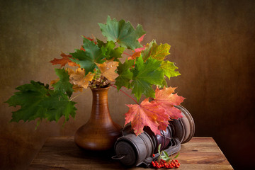 Herbstliches Stilleben mit Ahornblättern und Petroleumlampe