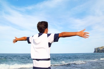 boy teenager open arms rear view looking blue sea