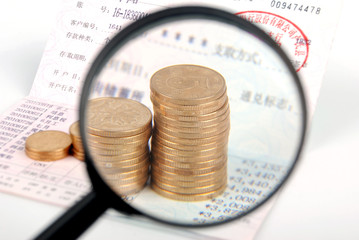 Magnifier and coins on bankbook