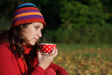 Girl having a cup of tea in a park with lots of autumn leaves