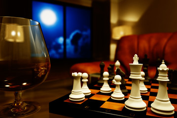 Interior with a glass of cognac and chess at night
