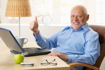 Happy senior man giving thumb up