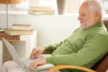 Smiling pensioner using laptop computer