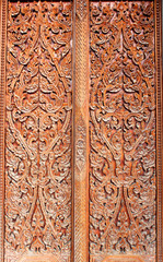 Thai art wood carving on door of temple