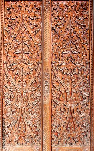 Thai art wood carving on door of temple