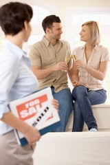 Estate agent with celebrating couple