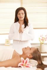 Masseur meditating over patient