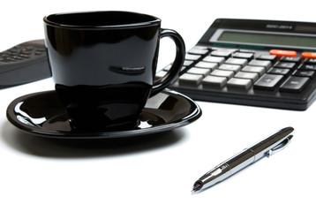 coffee mug, calculator, pens, phone