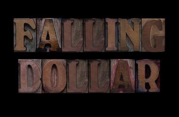 the words falling dollar in old letterpress wood type