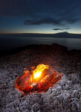 small campfire on rocky coast at night