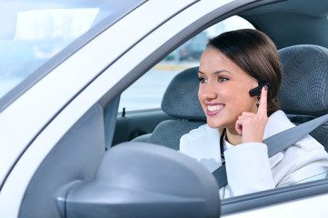 beautiful woman is safely talking phone in a car using a bluetoo