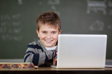 junge mit notebook in der schule